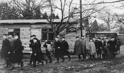Boys walking among the huts