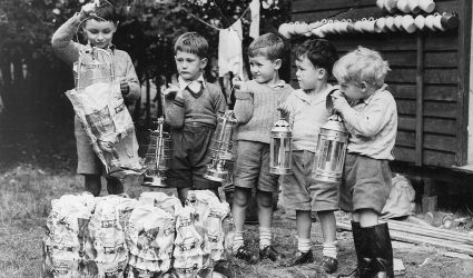 Young boys holding lanterns.