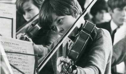 Boy playing a Violin in a Concert.